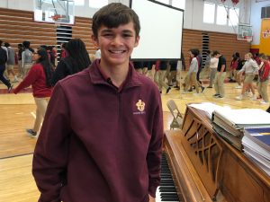 Scecina student Anthony Higgins stands by piano in Scecina gym