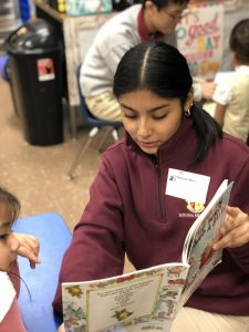 Student with book reading to child