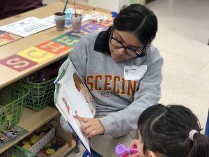 student reading to preschooler